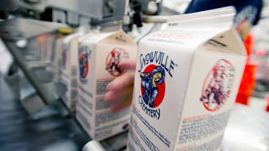 Employees load sealed milk cartons off the production line into crates for delivery at the Snowville Creamery in Pomeroy, Ohio, U.S.