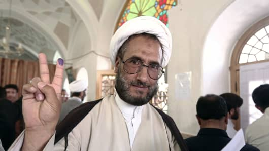 An Iranian clergyman shows his ink-stained finger after voting in the first round of the presidential elections in the Islamic Republic at a polling station at the Massoumeh shrine in the holy city of Qom on June 14, 2013.
