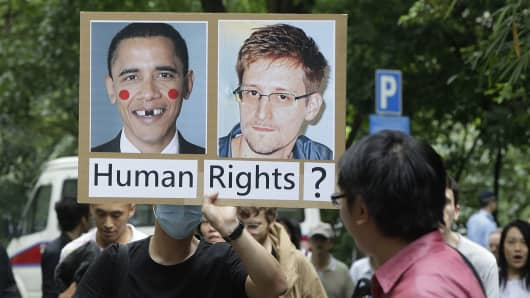 A man holds up a protest sign during the protest rally to support Edward Snowden in Hong Kong on June 15, 2013.