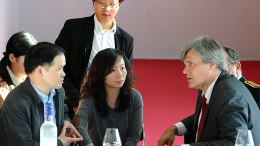 French Agriculture Minister Stephane Le Foll (R) speaks with a delegation from the Chinese Embassy in France on the sidelines of the Vinexpo wine fair in Bordeaux on June 16, 2013, after a group of Chinese students were attacked.