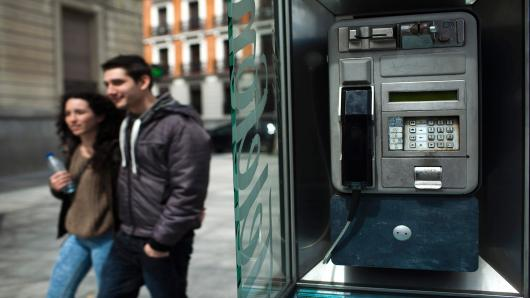 Pedestrians pass a Telefonica SA fixed-line public telephone in Madrid, Spain