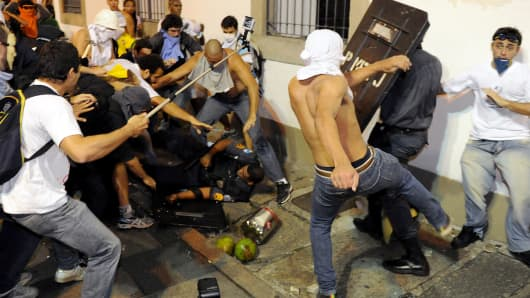 Demonstrators clash with riot police during a protest in front of Rio de Janeiro's Legislative Assembly (ALERJ) building in Rio de Janeiro, on June 17, 2013