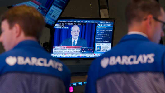 Traders work on the floor of the New York Stock Exchange (NYSE) as Ben S. Bernanke, chairman of the U.S. Federal Reserve, speaks on television in New York, U.S.