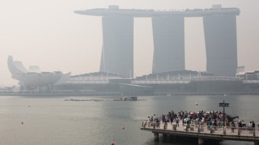 Tourists gather to take photographs of the haze covered Marina Bay Sands hotel on June 18, 2013 in Singapore.