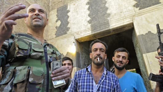 A Syrian rebel commander distributing the salaries of rebels in US dollars.