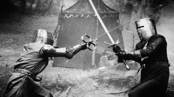 Two knights in metal masks duel in a scene from the medieval comedy, 'Monty Python and The Holy Grail.'