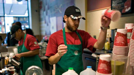 Workers fill orders inside a Starbucks in New York, U.S.