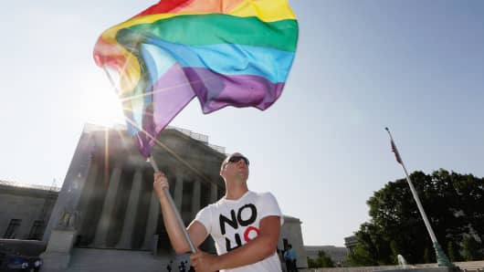 Gay rights activist Vin Testa of DC waves a flag outside the U.S. Supreme Court building on June 25, 2013 in Washington, DC.
