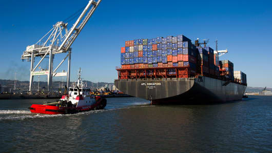 A tug boat moves the APL Singapore container ship to dock at the Port of Oakland in Oakland, California, U.S.