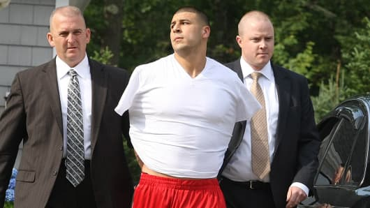 New England Patriots tight end Aaron Hernandez being led out of his home in handcuffs.