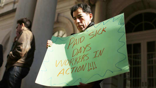 A man holds a sign at a rally in front of City Hall to show support for a paid sick leave bill in New York City.