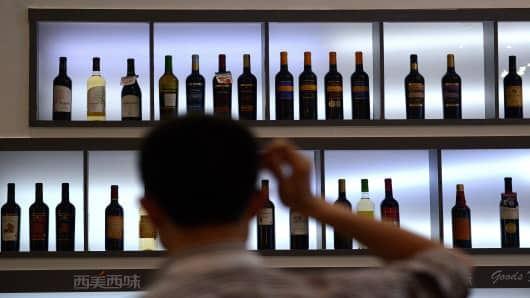 A man looks at shelves of wines at a wine expo in Beijing