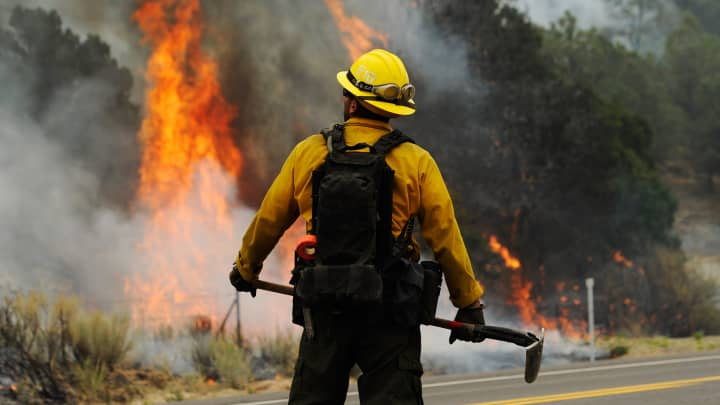 A firefighter watches flames grow after setting a backburn in an attempt to control a raging wildfire.
