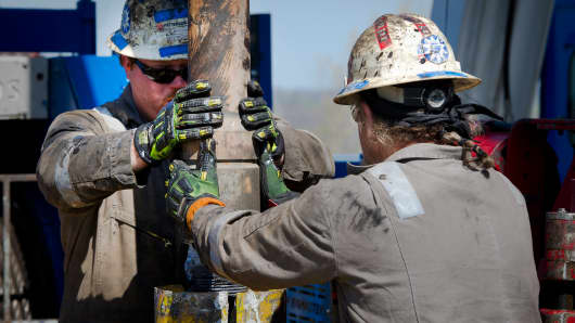 Workers change pipes at a Consol Energy horizontal gas drilling rig.
