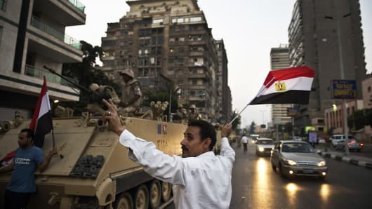 Egyptians salute army vehicles upon their deployment on a street leading to Cairo University on July 3, 2013.