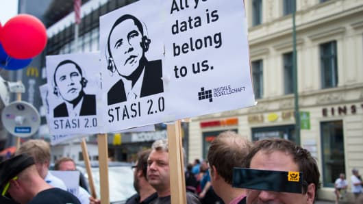 Protestors hold posters reading 'Stasi 2.0' depicting US President Barack Obama wearing headphones in Berlin, Germany.