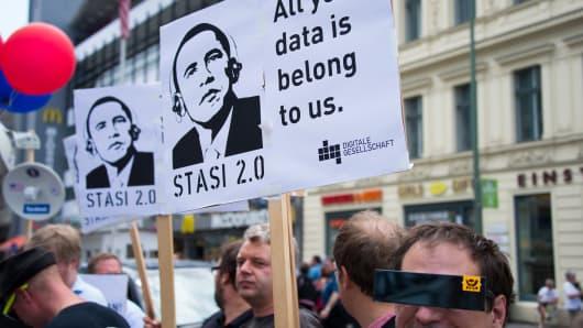Protestors hold posters reading 'Stasi 2.0' depicting US President Barack Obama wearing headphones in Berlin, Germany.