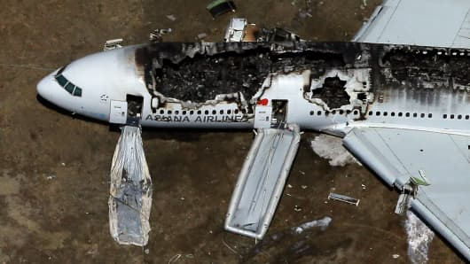 A Boeing 777 airplane lies burned on the runway after it crash landed at San Francisco International Airport July 6, 2013 in San Francisco, California.