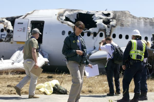 An NTSB investigator examines scattered debris on the scene of the Asiana Airlines crash on July 7, 2013 in San Francisco, California. The Boeing 777 passenger aircraft from Asiana Airlines coming from Seoul, South Korea crashed landed on the runway at San Francisco International Airport. Two people died and dozens were injured in the crash.