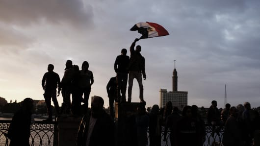 Egyptian protesters stand on a fence by the Nile River during a protest near Tahrir Square on February 1, 2013 in Cairo,