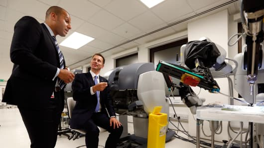 Health Secretary Jeremy Hunt is demonstrated a robotic da Vinci Surgical System by Clinton John, Simulation and Clinical Skills Centre Manager (L), during his tour of the Education Centre and headquarters of University College Hospital, prior to delivering a speech on the 'silent scandal' of errors in the NHS, on June 21, 2013 in London, England.