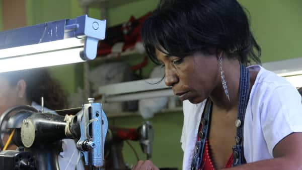 A seamstress hard at work with a 1950s-era Singer sewing machine.