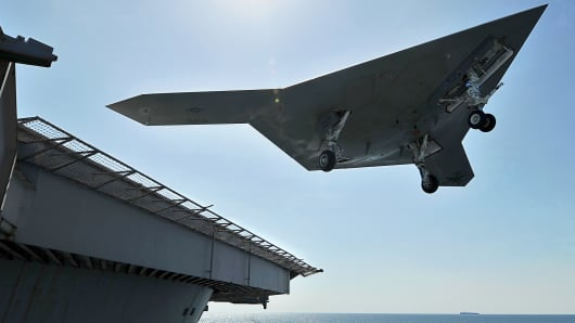 "An X-47B unmanned combat air system (UCAS) demonstrator performs a ""touch and go"" May 17, 2013 on the flight deck of the aircraft carrier USS George H.W. Bush. An aircraft does not stop moving during a touch and go. Wednesday's landing will attempt a full stop."