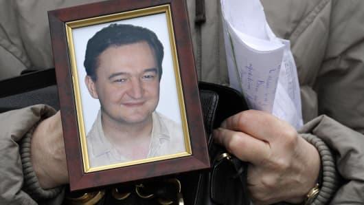 File photo of Nataliya Magnitskaya holding a portrait of her son, Sergei Magnitsky.