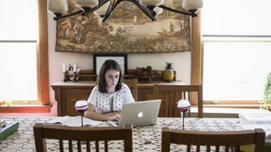 Kelly Binns, 19, does school work while housesitting in Denver, Colo. Binns is already worried about how she will pay back her student loans when she graduates in 2016.