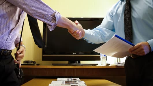 A representative from Independent Capital Management shakes hands with a interviewee at s job fair in El Segundo, Calif.