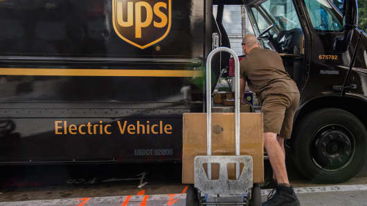 A UPS driver loads packages to be delivered onto a dolly from a United Parcel Service (UPS) all-electric vehicle in Sacramento, California, U.S.,