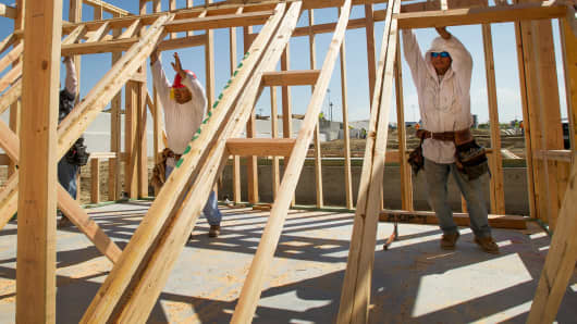Contractors raise a wall while working on a new home under construction in Dublin, California.
