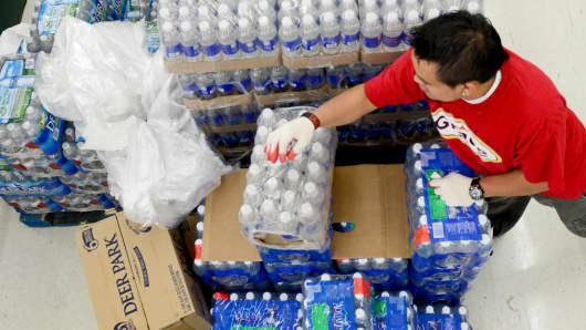 Osman Raul restocks drinking water at Jumbo Foods International Supermarket in Temple Hills, MD on July 16, 2013.