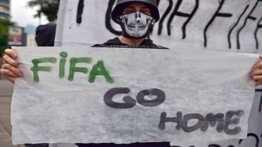 A demonstrator walks with a banner asking FIFA to go home during a protest.