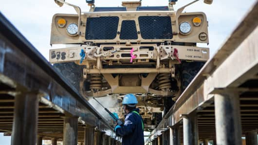 A civilian contractor power washes a Mine-Resistant All-Terrain Vehicle.