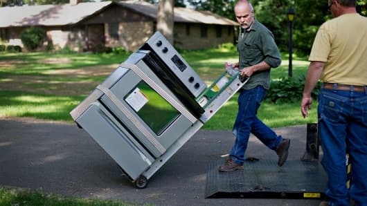 Valley Appliance employees Dennis Husser, left, and Dan Arkels deliver a Maytag Corp. electric stove to a customer in Princeton, Illinois, U.S.