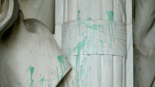A splatter of green paint covers a large area on the statue of President Abraham Lincoln after it was vandalized at the Lincoln Memorial.