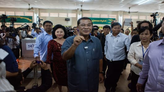 Cambodian Prime Minister Hun Sen shows his stained finger after voting during the Cambodian general elections in Phnom Penh, Cambodia.