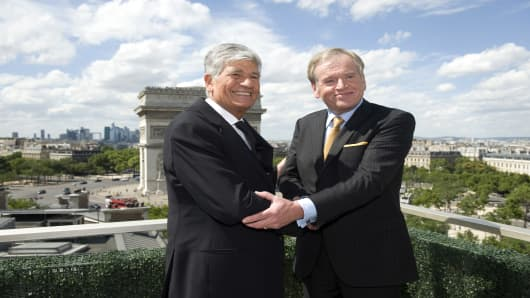 Maurice Levy, chief executive officer of Publicis Groupe SA, left, and John Wren, chief executive officer of Omnicom Group Inc., shake hands after signing the merger agreement.
