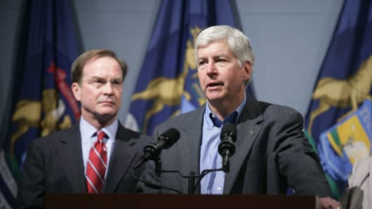 Michigan Attorney General Bill Schuette stands behind Gov. Rick Snyder as he addresses the media.