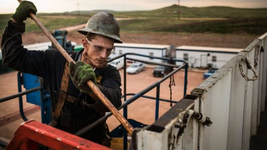 A floor hand for Raven Drilling, works on an oil rig drilling into the Bakken shale formation outside Watford City, North Dakota.
