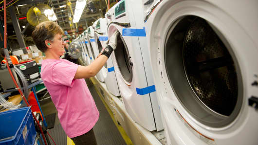 An employee works on a Whirlpool washing machine at the company's operations plant in Clyde, Ohio.