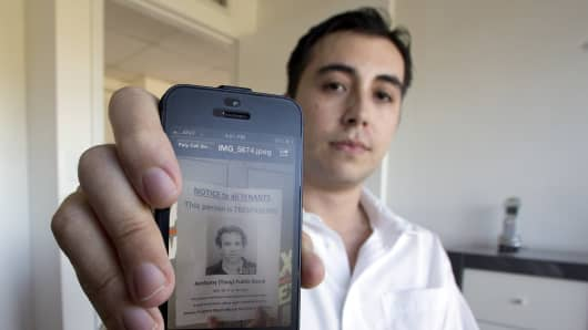 David Sierra displaying an image on his cellphone showing a flier that the management company passed out to tenants in an office complex where they rented space to Biogenesis and Anthony Bosch.