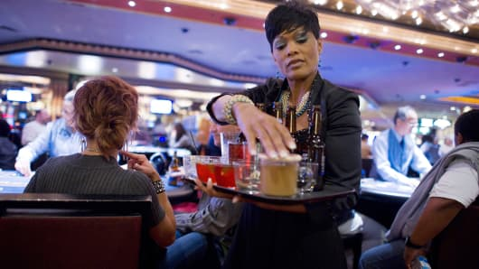 A cocktail waitress delivers drinks to guests at the MGM Resorts International casino in Las Vegas, Nevada.
