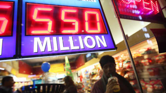 A sign outside the One Stop Mart shows the winning amounts for lottery games including the $550 million for the Powerball jackpot in Chicago, Illinois.