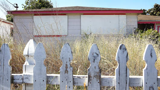 Weeds grow past the height of a picket fence in front of an abandoned house in Richmond, California.