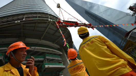 Construction workers watch as the final steel beam is put in place for the topping out of the Shanghai Tower.