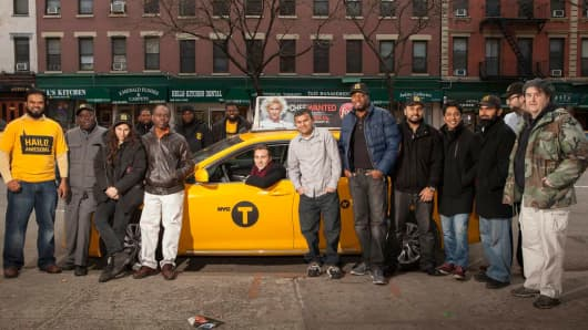 Hailo CEO Jay Bregman poses with his employees in a taxi cab outside the company's New York headquarters.