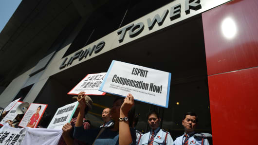 Demonstrators stand outside of the Li Fung tower in Hong Kong as they protest over what they say are unpaid wages owed to textile workers in Turkey by Li and Fung and garment brand Esprit.