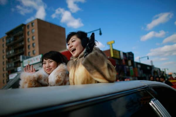 Women wave while riding in the Flushing Chinese New Year Parade in the Queens borough of New York City.
